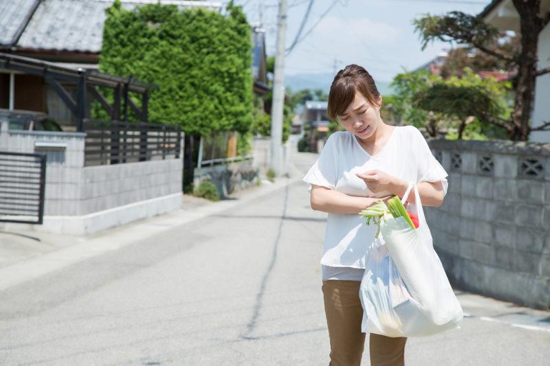 買い物袋が重そうな女性の写真